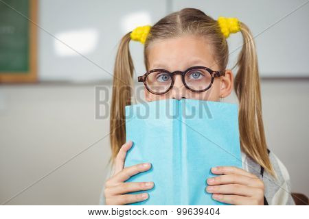 Portrait of cute pupil covering face with a book in a classroom in school