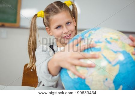 Portrait of cute pupil holding globe in a classroom in school