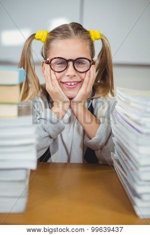Portrait of smiling pupil between stack of books on her desk in a classroom
