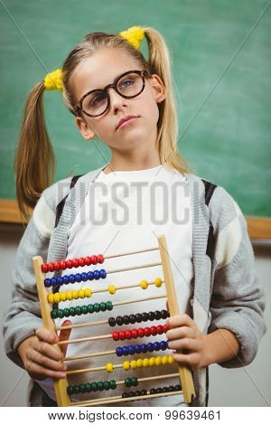 Cute pupil holding abacus in a classroom in school