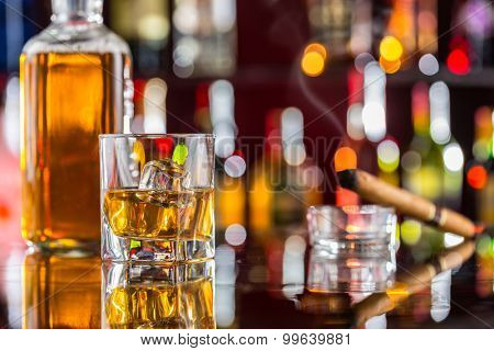 Whiskey drink on bar counter with blur bottles on background