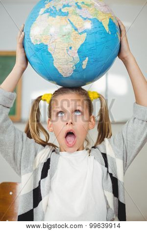 Cute pupil balancing globe on head in a classroom in school