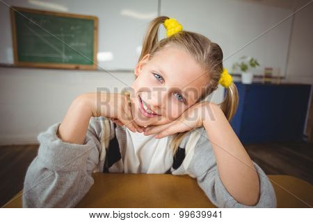Portrait of smiling pupil sitting at her desk in a classroom in school