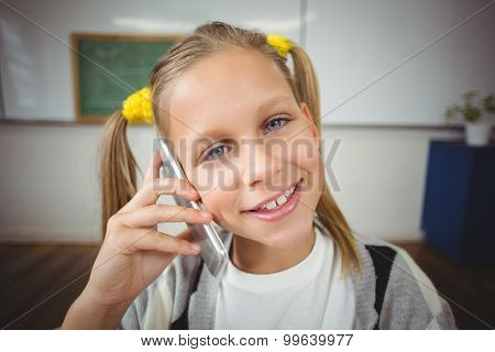 Portrait of smiling pupil phoning with smartphone in a classroom in school