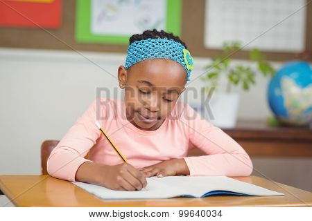 Focused pupil working at her desk in a classroom in school