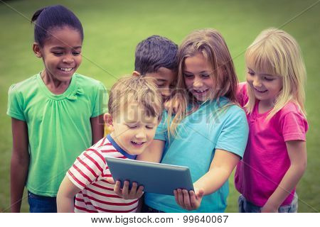 Smiling classmates using tablet together on campus