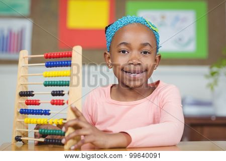 Portrait of smiling pupil calculating with abacus in a classroom in school