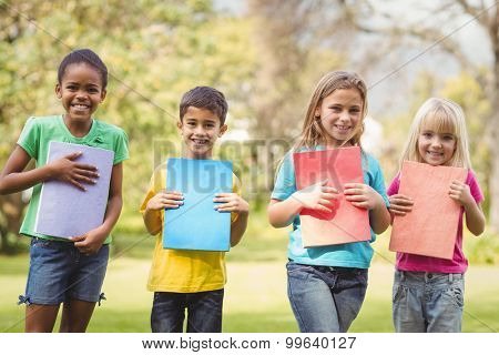 Portrait of smiling classmates holding notepads on campus