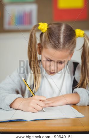 Concentrated pupil working at her desk in a classroom in school