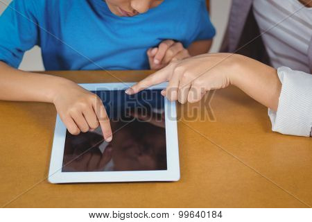 Teacher and pupil using tablet at his desk in a classroom