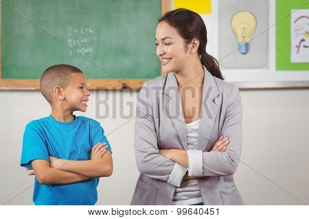 Pretty teacher and cute pupil in front of chalkboard in a classroom