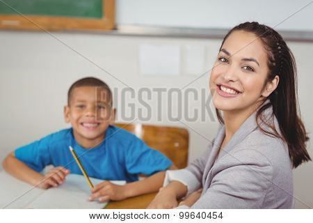 Portrait of smiling teacher and her pupil sitting at desk in a classroom