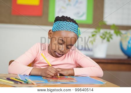 Focused pupil colouring a picture at her desk in a classroom