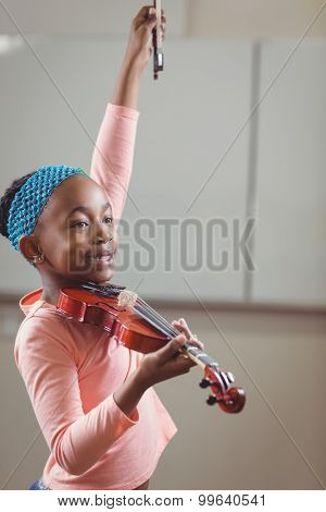 Smiling pupil playing violin in a classroom in school