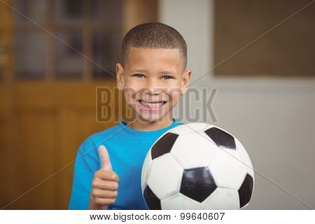 Portrait of smiling pupil holding football and doing thumbs up in a classroom