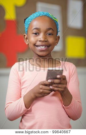 Portrait of cute pupil with smartphone in a classroom in school