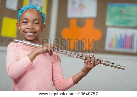 Portrait of cute pupil with flute in a classroom in school