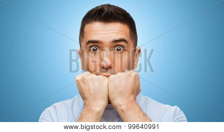fear, horror, emotions and people concept - scared man face over blue background
