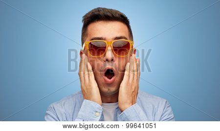 summer, emotions, style and people concept - face of scared or surprised middle aged latin man in shirt and sunglasses over blue background