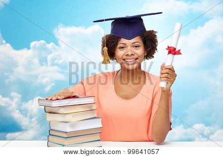 education, school, knowledge, graduation and people concept - happy smiling african american student girl in bachelor cap with books and diploma sitting at table over blue sky and clouds background