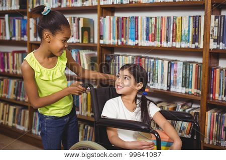 Smiling pupil in wheelchair holding books in the library in school