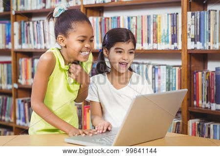 Smiling pupils using laptop in the library in school