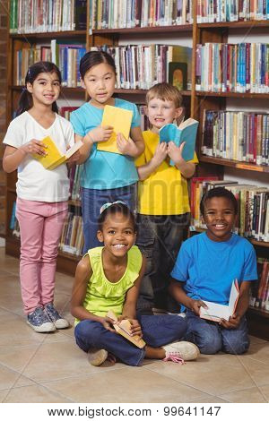 Portrait of smiling pupils with books in the library in school