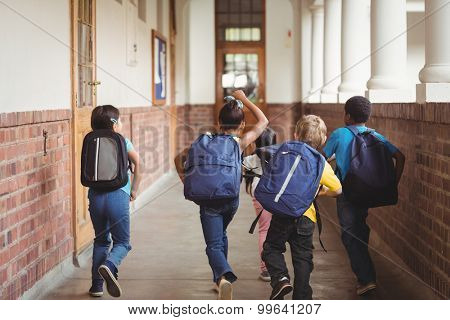 Rear view of happy pupils walking at corridor in school