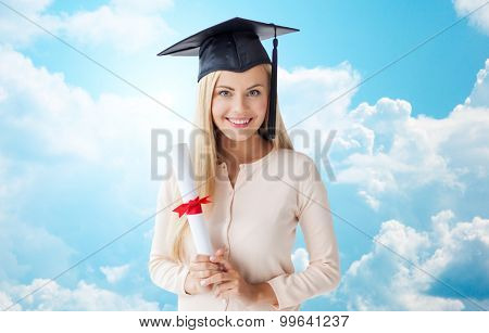 people, education, high school and graduation concept - happy student girl in bachelor cap with diploma over blue sky and clouds background
