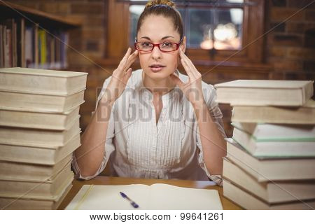 Portrait of focused blonde teacher sitting between books in the library in school