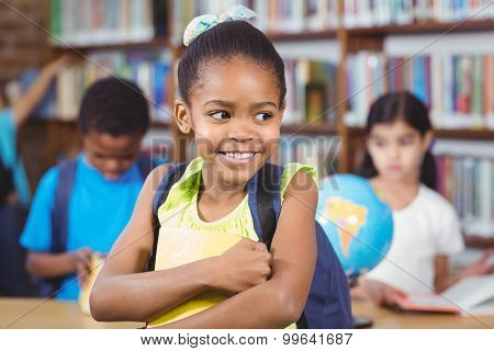 Cute pupil holding book in the library in school