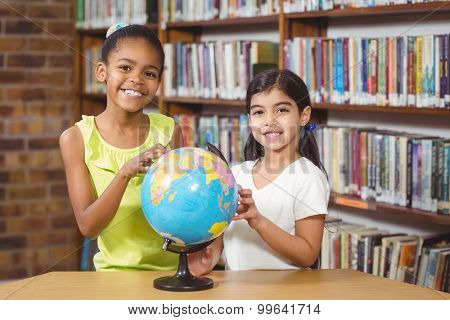 Portrait of smiling pupils studying globe in the library in school