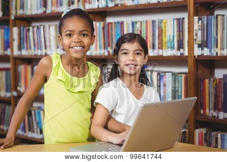 Portrait of smiling pupils using laptop in the library in school
