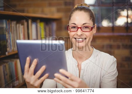 Portrait of blonde teacher using tablet in the library in school