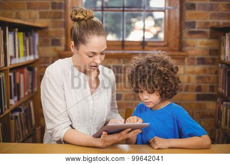 Blonde teacher and pupil using tablet in the library in school