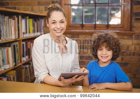 Portrait of blonde teacher and pupil using tablet in the library in school