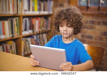 Cute pupil using tablet in the library in school