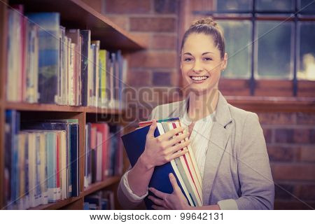 Portrait of blonde teacher holding books in the library in school