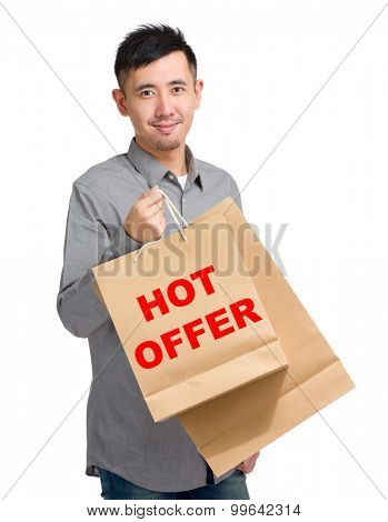 Asian man hold with shopping bag and showing hot offer