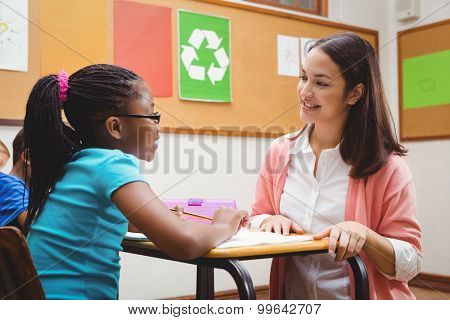 Happy teacher helping her students at the elementary school