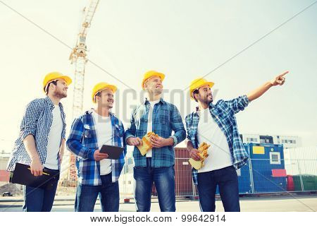 business, building, teamwork, technology and people concept - group of smiling builders in hardhats with tablet pc computer and clipboard outdoors