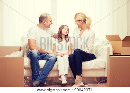 family, child, accomodation and home concept - smiling parents and little girl moving into new home