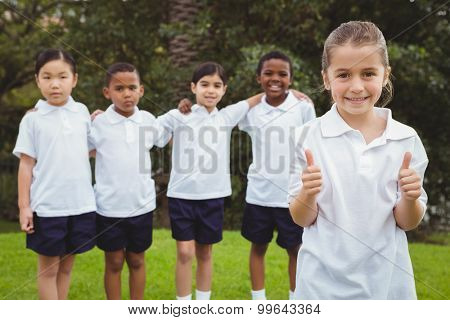 Student standing with thumbs up on school grounds