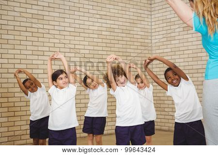 Teacher and students doing stretches at the elementary school