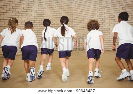 Students running across the court in elementary school