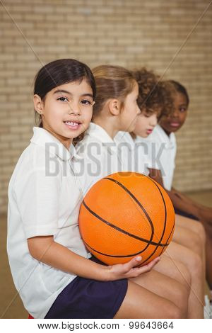 Student holding basketball with fellow players at the elementary school