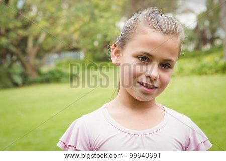 A Smiling kid standing outside in the park