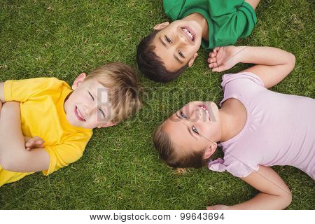 Smiling pupils lying on the ground looking at the camera