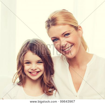 family, child, technology and home concept - smiling mother and little girl with laptop at home