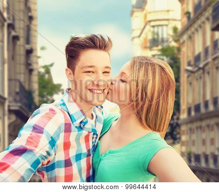 travel, tourism, summer vacation, technology and love concept - happy couple taking selfie with smartphone or camera and kissing over city street background